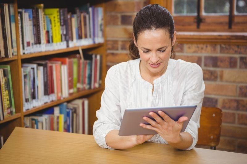 Profesora con una tablet y estantería con libros detrás