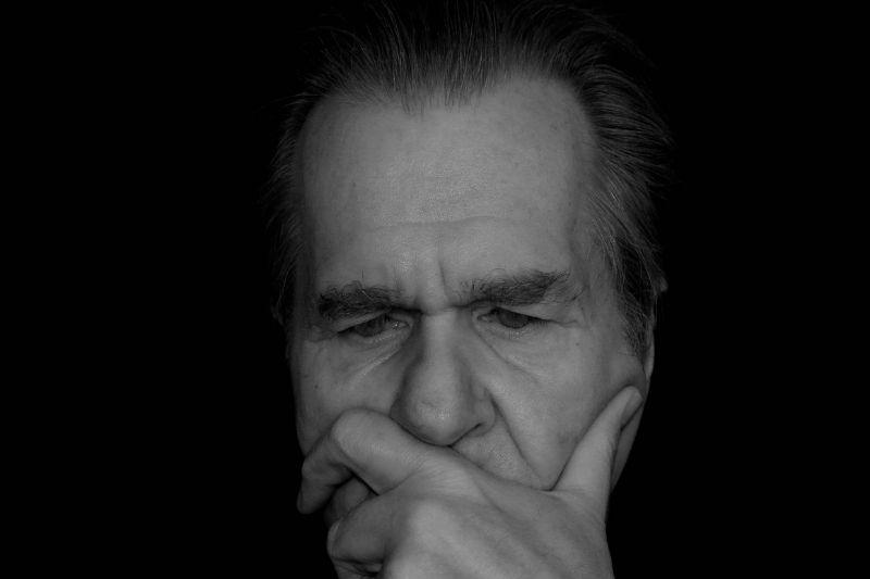 hombre mayor descubre un punto de dolor en foto en blanco y negro