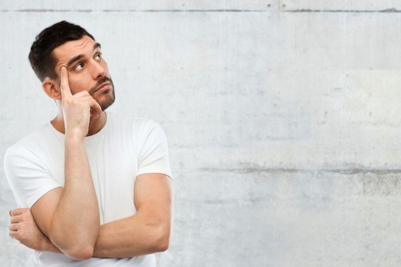 Chico joven caucásico con camiseta blanco pensando sobre pared neutra
